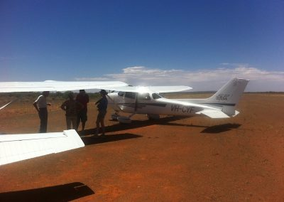 Pilot briefing under the wing in the Nullarbor midday sun